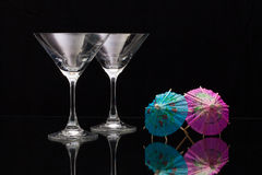 Two empty glasses of champagne with paper umbrellas Royalty Free Stock Images
