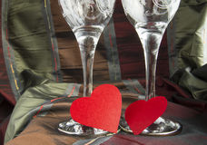 Two empty glasses of champagne and red hearts, Valentine`s day stock images
