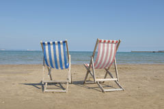 Two empty linen beach chairs one blue and one red in the middle of the image on the beach, facin Royalty Free Stock Photo