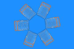 Two empty market baskets made from chrome metal wire and orange rubber handles lying in form of flower or star on center of blue t. Able. Top view. Concept of royalty free stock image