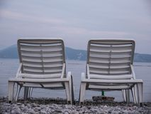 Two empty plastic chaise lounge on sea side at the end of season. Two open empty white plastic chaise lounge laid out on sea side pebbles and mountains on royalty free stock images