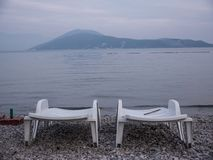Two empty plastic chaise lounge on sea side at the end of season. Two empty white plastic chaise lounge laid out on sea side pebbles and mountains on background royalty free stock photography