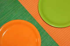 Two empty plates, green and orange. Two empty plates. Orange stands on a green napkin,green on orange napkin.arranged diagonally. top view Royalty Free Stock Photo