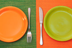 Two empty plates, green and orange. Two empty plates. Orange stands on a green napkin,green on orange napkin. fork and knife near the plates.top view Royalty Free Stock Images