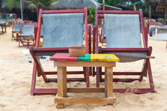 Two empty red deckchairs at beach. Stock Photo