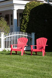 Two empty red lawn chairs. On the front lawn Royalty Free Stock Photo