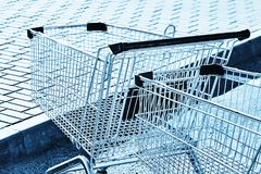 Two Shopping carts in a store parking lot. Blue toning stock image