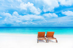 Two empty sunbed on the beach. Beautiful seascape, relaxation on Maldives island, luxury summer vacation concept Royalty Free Stock Image