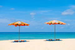 Two empty sunbeds and beach parasol sunshades on sand beach Stock Photography
