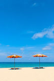 Two empty sunbeds and beach parasol sunshades on sand beach Royalty Free Stock Image