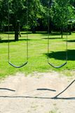 Two empty swings in park Royalty Free Stock Photo
