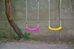 Two empty swings in purple and yellow Royalty Free Stock Image