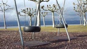 Two empty tires on a playground. Moved by the wind and surrounded by trees stock video
