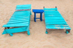 Two empty turquoise sunbeds at beach. Royalty Free Stock Photography