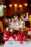 Two empty wedding glasses, decorated with greenery, red roses and ribbon, standing on the banquet table. Two empty wedding glasses, decorated with greenery, red Royalty Free Stock Photo