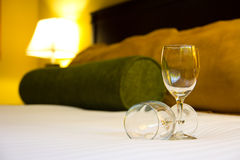 Two empty wine glasses on bed. With yellow light illuminate at the back Royalty Free Stock Photo