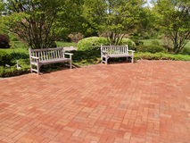 Two empty wood benches by a red patio. Two empty wood benches by a red brick patio in a garden Stock Images