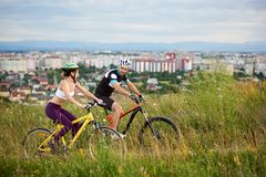 Two energetic cyclists in helmets riding bikes in high grass. royalty free stock photography