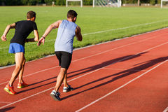 Two energetic men jogging outdoors on sunny day Stock Images