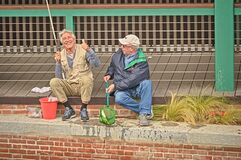 Two energic old men enjoy a moment of fishing in the park of a big city