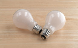 Two energy saving light bulbs on a wood table Stock Photos