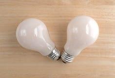 Two energy saving light bulbs on a wood table Stock Images