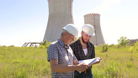 Two engineer builders with blueprint outdoors. Two men of the engineer working with drawings at the construction site stock footage