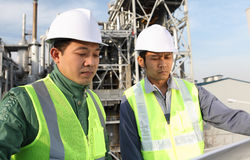 Two engineer discussing a new project. Two engineer oil industry discussing a new project with large oil refinery background Royalty Free Stock Photo