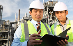 Two engineer discussing a new project. Two engineer oil industry discussing a new project with large oil refinery background Stock Image