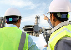Two engineer discussing a new project. Two engineer oil industry discussing a new project with large oil refinery background Royalty Free Stock Images