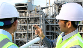 Two engineer discussing a new project. Two engineer  discussing a new project in front of oil refinery Stock Images
