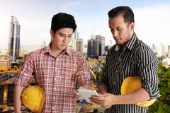 Two engineer discussing project. Two civil engineers discussing project and one engineer holding tablet, construction site on background Stock Photo