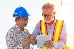 Two engineer mix race looking at tablet screen using technology. With CAD for construction and design concept Stock Photography