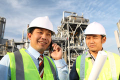 Two engineer oil industry. Industrial engineer communicate with mobile phone Stock Images