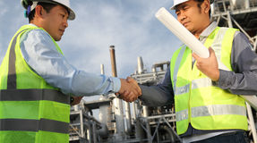 Two engineer oil industry. Closing a deal in front of an large oil refinary Stock Photography