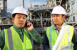 Two engineer oil refinery. Industrial engineer communicate with mobile phone serious Stock Photo