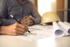 Two engineering man or co-workers working on a project and discussing together with looking at blueprint paperwork stock photography