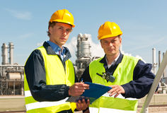 Two engineers. Wearing reflective clothing and a hard hat, looking up from the note board they have been discussing Stock Photo
