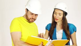 Two engineers or architects wearing had hats discuss project and look through papers in a yellow folder royalty free stock photography