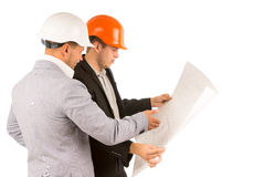 Two engineers or architects discussing a plan. Two young engineers or architects or structural engineers in hardhats and suits standing discussing a building Stock Photo