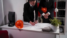 Two engineers businessmen in business office look at architect drawing with helmet stock video footage