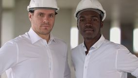 Two engineers, a caucasian and an african american, posing looking to the camera. Close up. Professional shot in 4K resolution. 104. You can use it e.g. in stock video