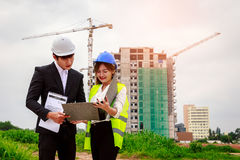 Two engineers checking plans, Crane and building construction si. Te on background Royalty Free Stock Photo