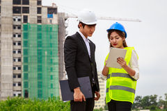 Two engineers checking plans using tablet computer at constructi Stock Images