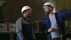 Two engineers discuss important stages of construction in heavy industry factory. welder background stock footage