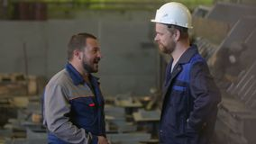 Two engineers discuss stages of construction in heavy industry factory. welder background. Two engineers discuss the important stages of construction in heavy stock video footage
