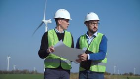 Two engineers discussing against wind farm. Two engineers discussing against turbines on wind farm on sunny day stock video