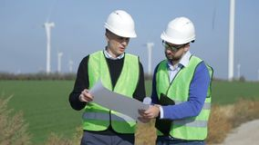 Two engineers discussing against wind farm. Two engineers discussing against turbines on wind farm on sunny day stock footage