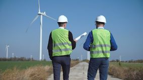 Two engineers discussing against wind farm. Back view of two engineers discussing against turbines on wind farm while walking along road on sunny day stock video footage