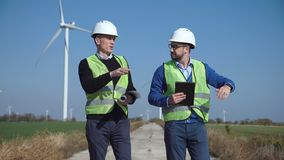 Two engineers discussing against wind farm. Two engineers discussing against turbines on wind farm while walking along road on sunny day stock footage